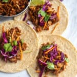 jackfruit tacos on tortilla with cilantro and purple cabbage