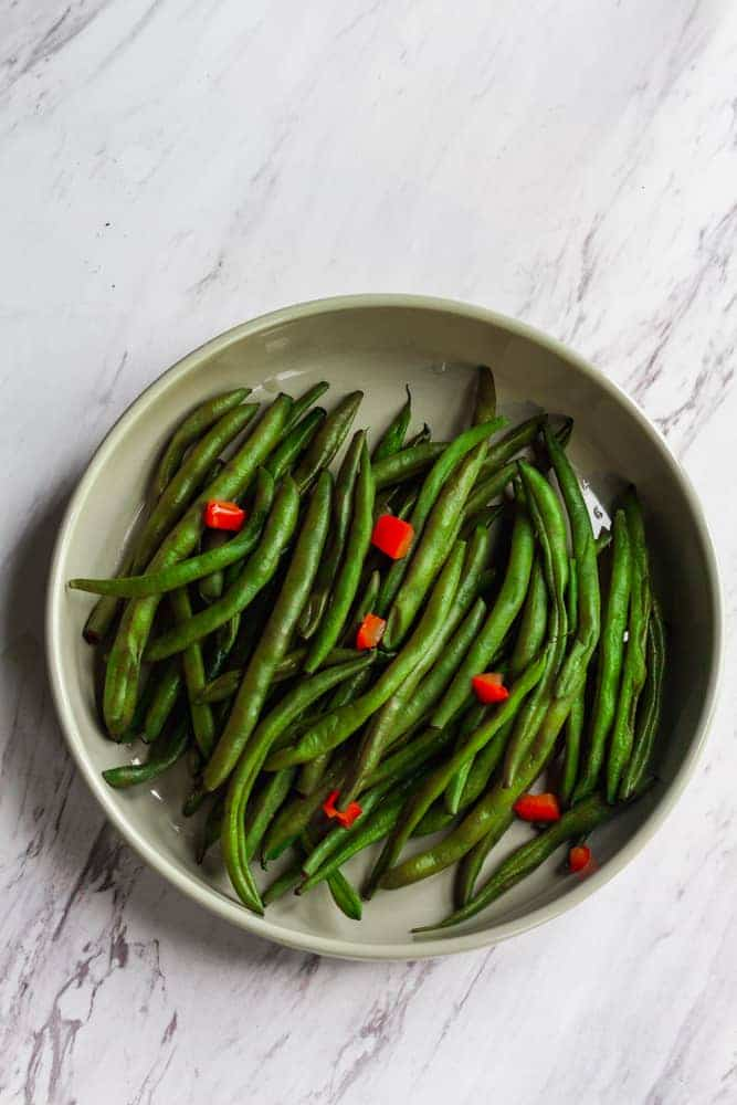 green bean  with diced red bell pepper in bowl