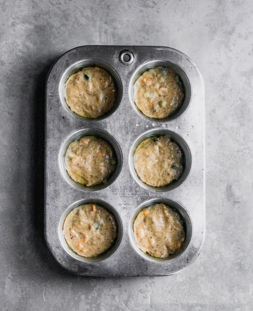 vegan cornbread muffins with vegan cheese and jalapenos in muffin tin