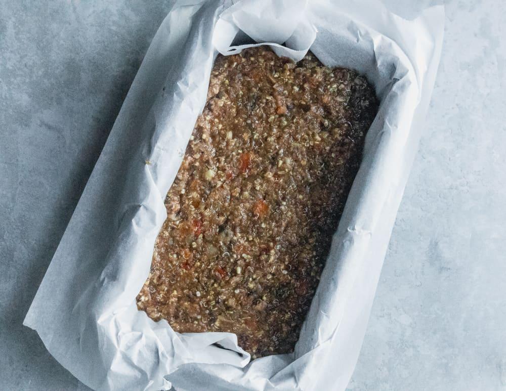 add vegan lentil meatloaf mixture made with mushrooms, veggies, garlic, onions, to loaf pan