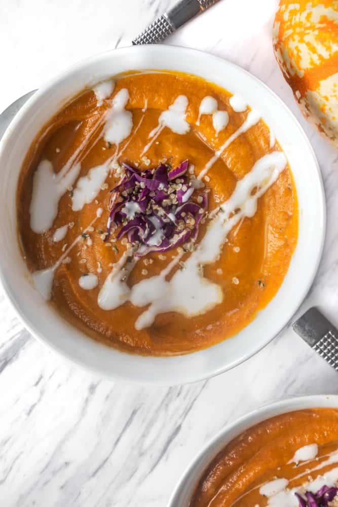 vegan pumpkin soup recipe from canned pumpkins with purple cabbage and rosemary, cream in white bowl with spoon