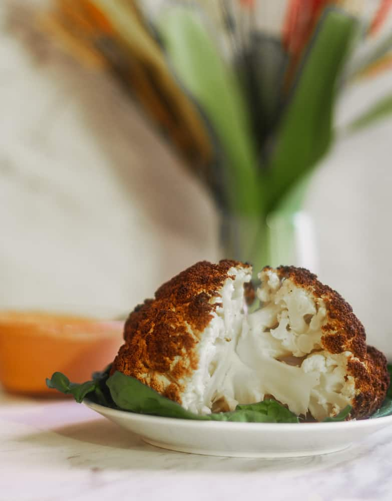 whole roasted cauliflower sliced on top of spinach with harissa dipping sauce