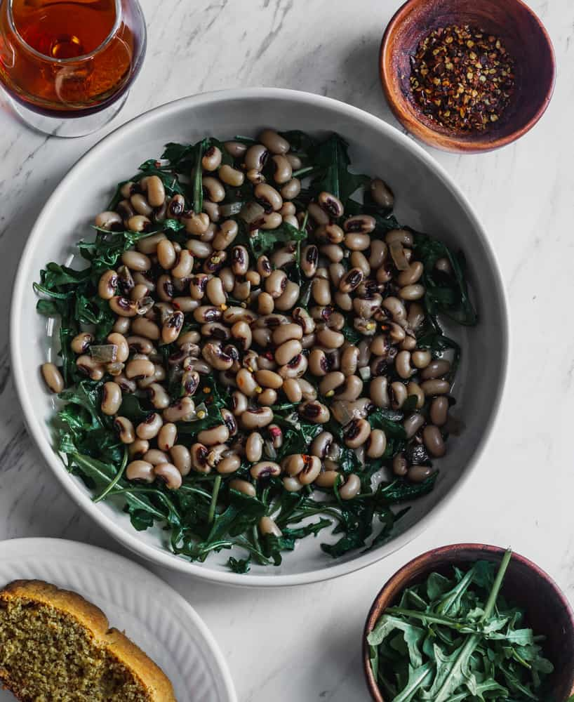 new years black eyed peas over greens in white bowl along cornbread, crushed red peppers