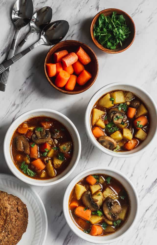 bowls of vegetables stew filled with mushrooms, potatoes and carrots