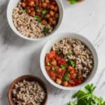 chana masala with rice and cilantro in white bowls