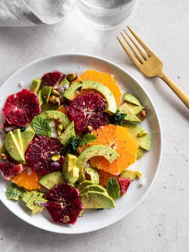 avocado and blood orange sliced with mint, pistachios and lemon vinaigrette on white plate.