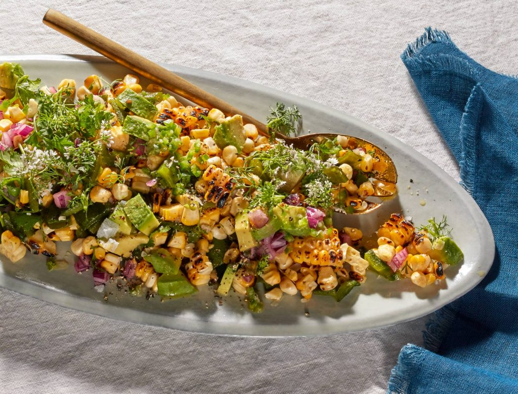 grilled corn poblano peppers, cilantro, red onions, avocado with spicy vegan dressing over gray tray