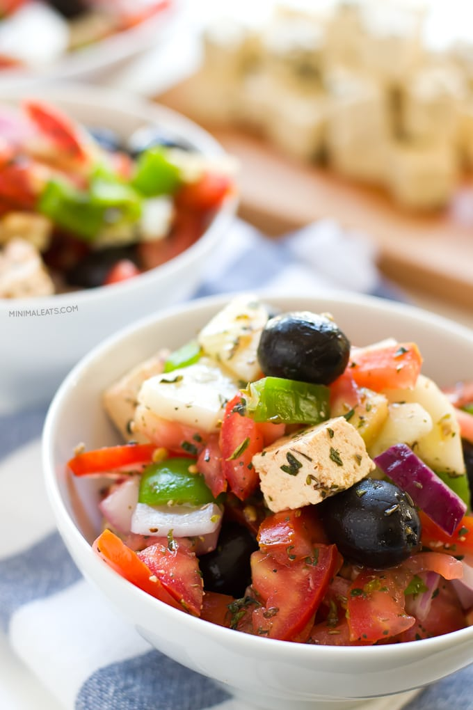 vegan greek salad recipe with tomatoes, chickpeas, olives, tofu feta, onions, herbs, bell peppers in white bowl
