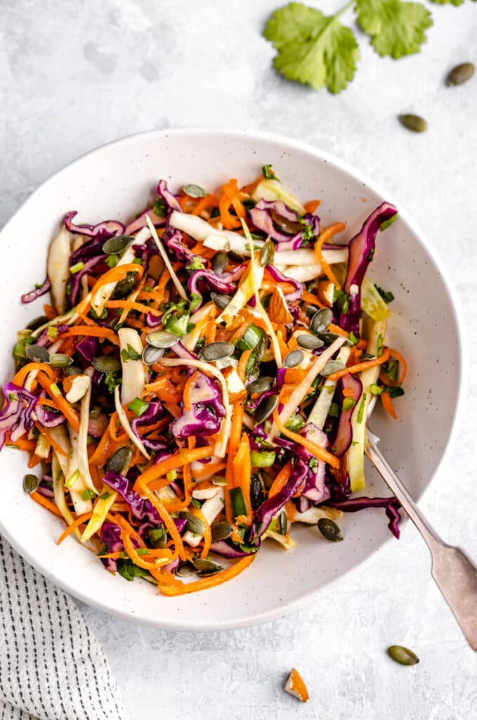 salad recipe of purple cabbage, green cabbage, green onion, cilantro, pepitas, sliced almonds, carrots, in a white bowl