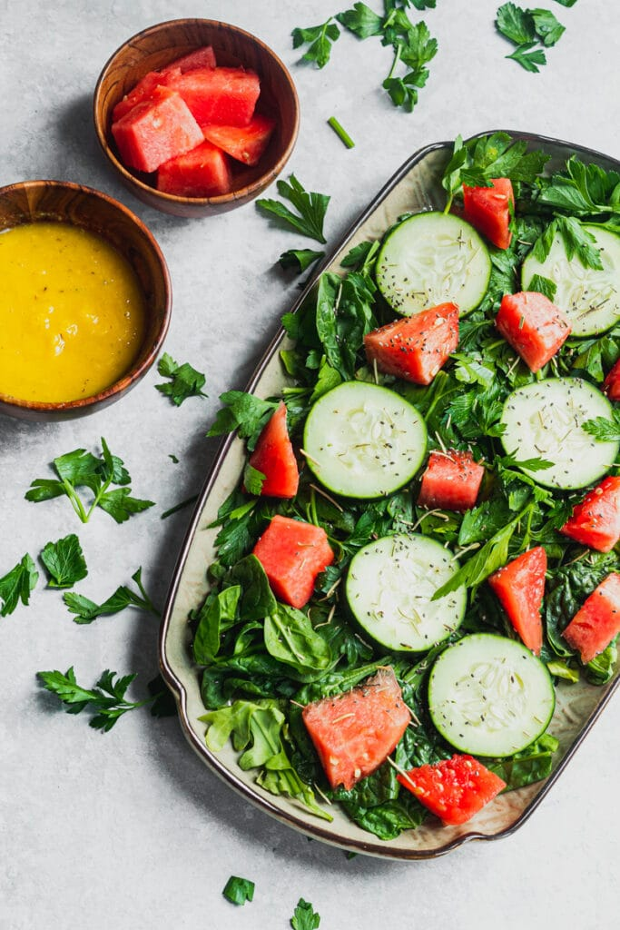 platter with parsley, arugula, watermelon, cucumber, chia seeds and mango salad dressing