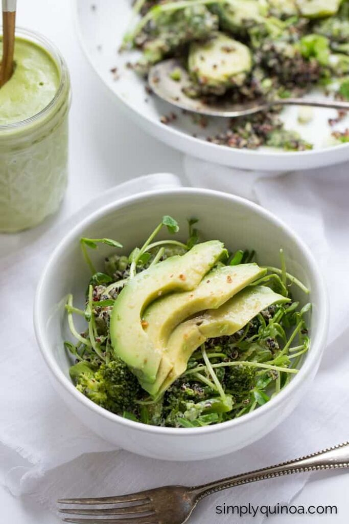 black quinoa, green onions, pea shoots, brussel sprouts, broccoli and avocado in white bowl