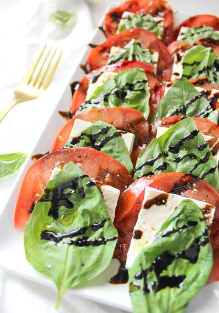 tofu, lettuce, tomatoes, and balsamic vinegar on white tray