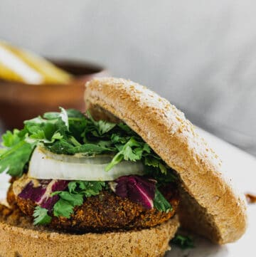 tempeh chorizo spiced vegan mexican torta with cilantro, purple lettuce, onions, buns, and roasted potatoes