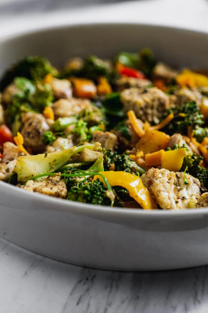 jerk tempeh with broccoli, cauliflower, and bell peppers in a bowl