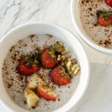 porridge with coconut milk, cinnamon, walnuts, and strawberries in white bowls.