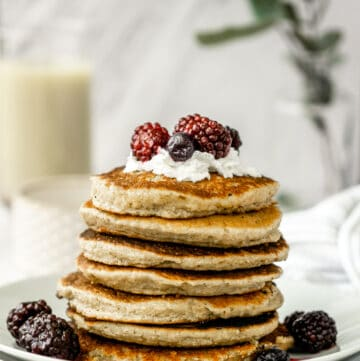 stack of vegan almond flour pancakes with coconut whip cream, fresh berries, oat milk on white plates